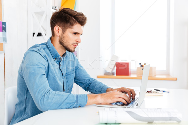 Portrait of a thoughtful casual businessman sitting at the desk Stock photo © deandrobot