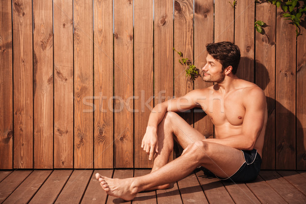 Handsome young man sitting at the poolside and looking away Stock photo © deandrobot
