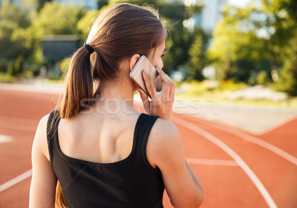 Back view of a female athlete talking on mobile phone Stock photo © deandrobot