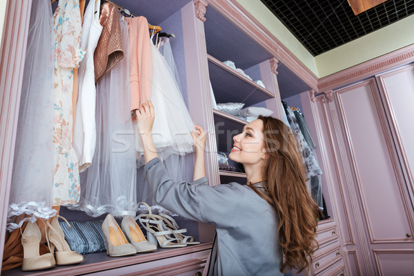 Young woman searching what to wear in a wardrobe Stock photo © deandrobot