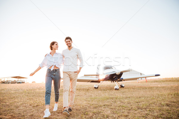 Couple walking together across the field with airplane on background Stock photo © deandrobot