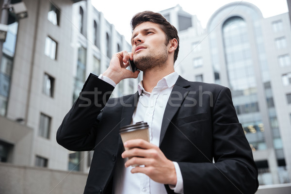 Businessman with take away coffee talking on cell phone Stock photo © deandrobot