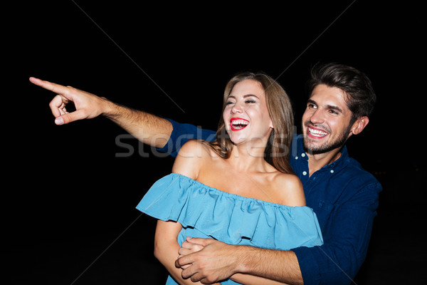 Happy joyful young couple laughing and pointing away Stock photo © deandrobot