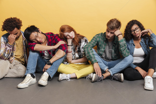 Multiethnic group of exhausted young friends sitting and sleeping Stock photo © deandrobot
