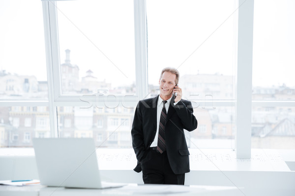 Smiling Elderly business man talking at phone near the table Stock photo © deandrobot