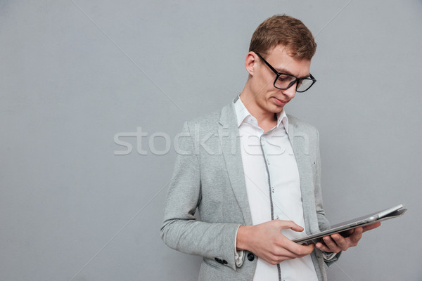 Man in suit and glasses with tablet Stock photo © deandrobot