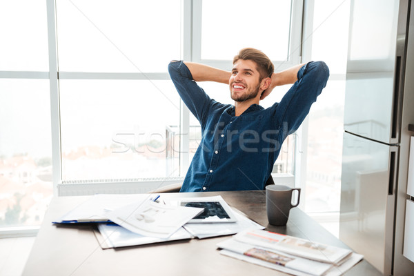 Cheerful young man sitting near table and stretching at home Stock photo © deandrobot