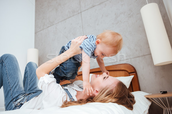 Mother playing and having fun with little son on bed Stock photo © deandrobot