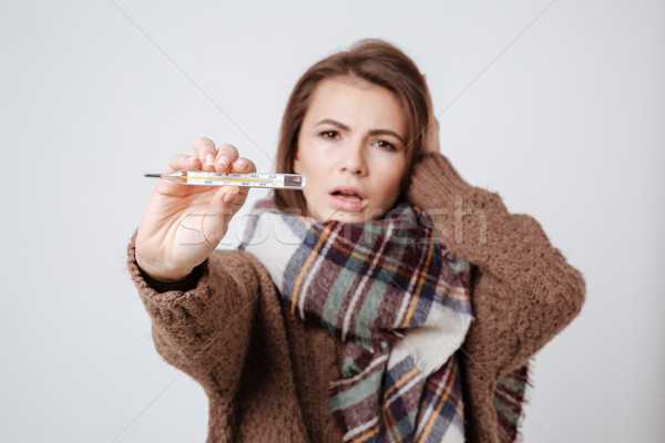 Sick woman in sweater and scarf showing thermometer Stock photo © deandrobot
