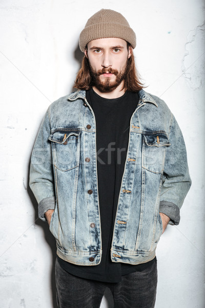Attractive bearded hipster man posing over wall background. Stock photo © deandrobot