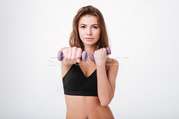 Pretty young lady make exercises with dumbbells Stock photo © deandrobot