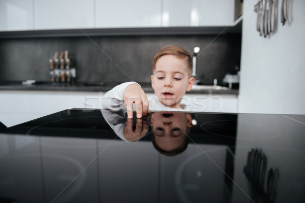 Dangerous situation with boy touching oven in the kitchen. Stock photo © deandrobot
