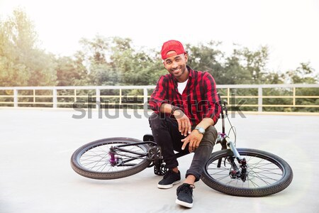 Attractive dark skinned boy sitting on his bicycle Stock photo © deandrobot