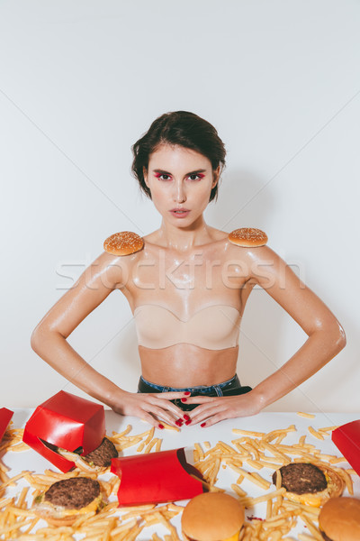Woman eating fast food and imitating shoulder straps with buns Stock photo © deandrobot