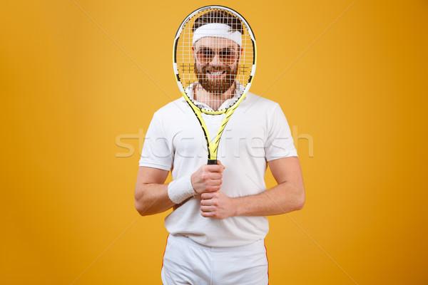 Smiling sportsman looking through tennis racquet Stock photo © deandrobot