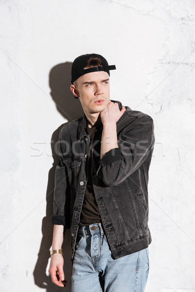 Vertical image of hipster in snap back looking away Stock photo © deandrobot