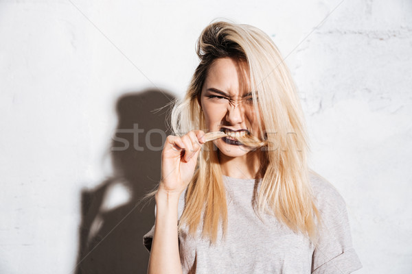 Angry beautiful young woman biting her long blonde hair Stock photo © deandrobot