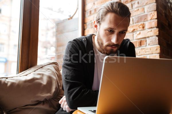 Ciddi sakallı adam dizüstü bilgisayar kullanıyorsanız kafe oturma Stok fotoğraf © deandrobot