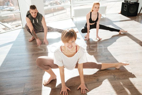 Group of cheerful young people practicing yoga with trainer Stock photo © deandrobot