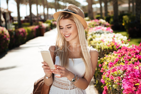 Happy young woman walking and using smartphone on summer resort Stock photo © deandrobot