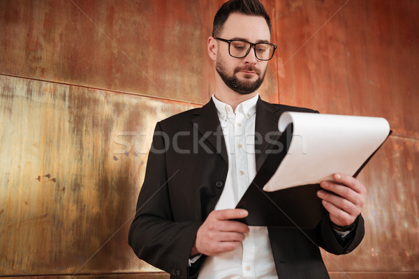 View from below of business man which looking at clipboard Stock photo © deandrobot