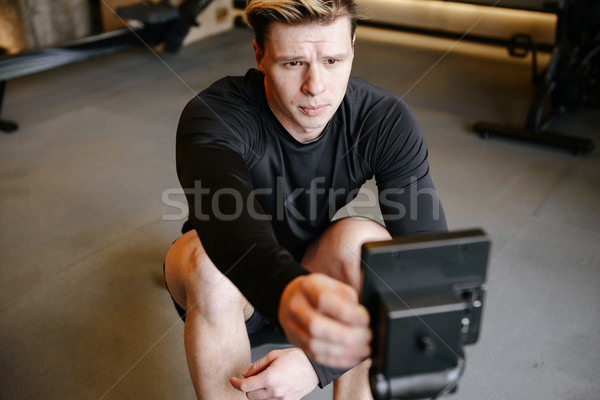 Serious Athletic man adjusts the rowing machine Stock photo © deandrobot