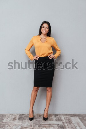 Successful young business woman standing with her hands in hips Stock photo © deandrobot