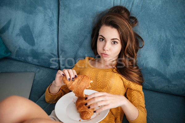 Girl laying on couch with plate full of pastry Stock photo © deandrobot
