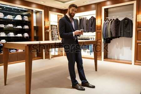Full-length shot of bearded man in glasses standing in wardrobe Stock photo © deandrobot