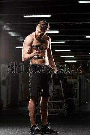 Concentrated strong sports lady sitting in gym Stock photo © deandrobot