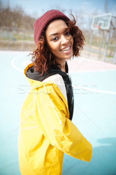 Cheerful african curly young woman wearing yellow coat Stock photo © deandrobot