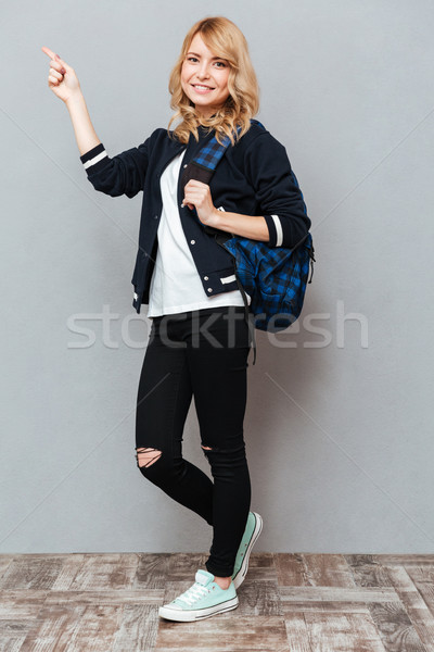 Happy young lady pointing Stock photo © deandrobot