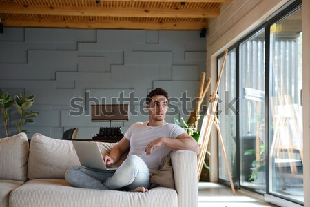 Young man using laptop while sitting in living room Stock photo © deandrobot