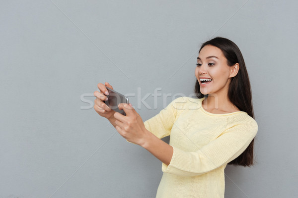 Cheerful beautiful young woman playing video games on mobile phone Stock photo © deandrobot