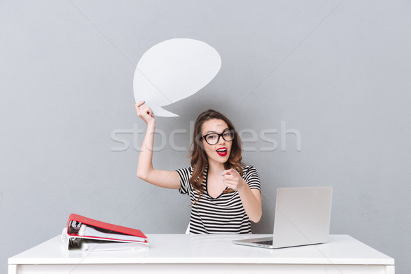 Happy young lady wearing glasses holding empty speech bubble Stock photo © deandrobot