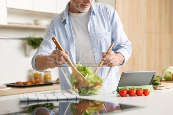 Imagem homem maduro cozinhar salada comprimido em pé Foto stock © deandrobot