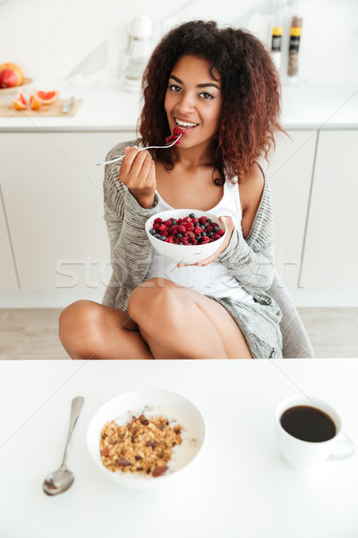 Young woman eating healthy food in kitchen Stock photo © deandrobot