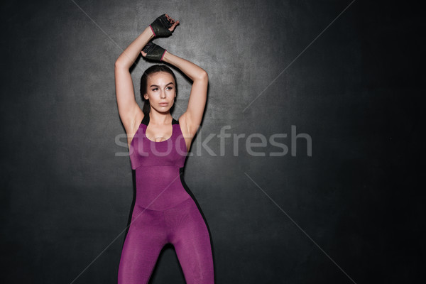 Strong sportswoman posing over grey background. Stock photo © deandrobot