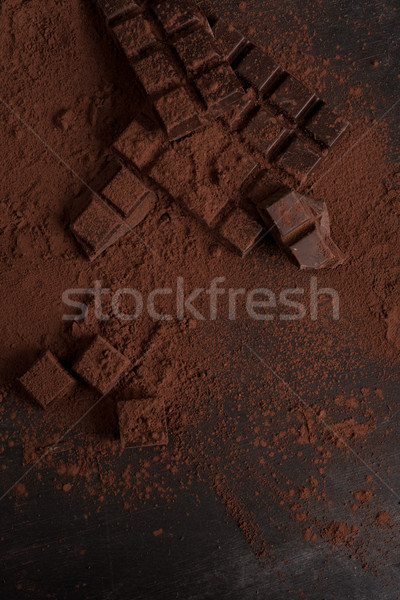 Top view of dark chocolate blocks crashed into pieces Stock photo © deandrobot