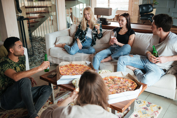 Smiling young friends eating pizza and talking at home Stock photo © deandrobot