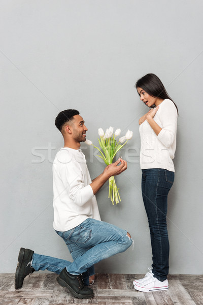 Man gives a flowers and wedding ring to woman. Stock photo © deandrobot