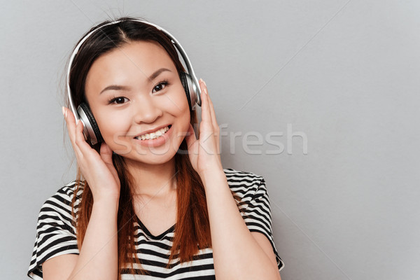 Happy young pretty woman listening music with headphones Stock photo © deandrobot