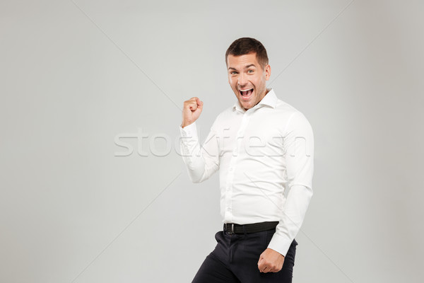Excited screaming young man make winner gesture. Stock photo © deandrobot