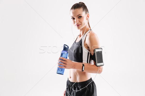 幸せ フィットネス女性 イヤホン 立って 水筒 ストックフォト © deandrobot