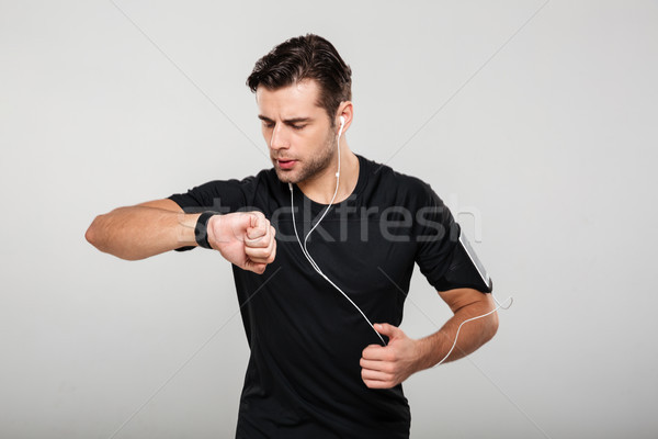 Portrait of a young sportsman in earphones listening to music Stock photo © deandrobot