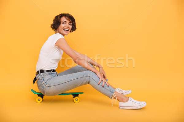Portrait of a smiling cheerful girl sitting on a skateboard Stock photo © deandrobot