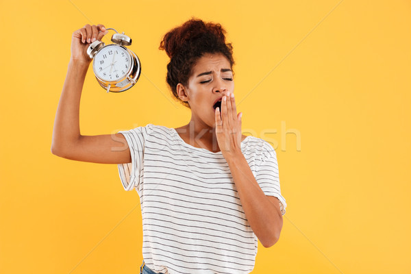 Tired african woman yawns and holding alarm clock Stock photo © deandrobot