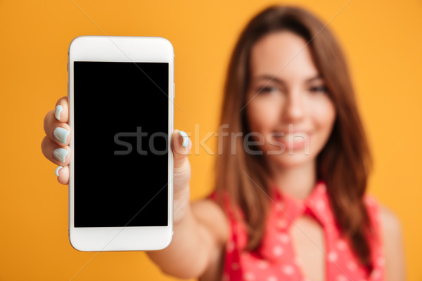 Close-up shot of pretty young woman showing blank screen on smar Stock photo © deandrobot
