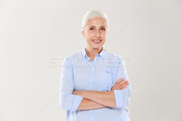 Portrait of happy elderly woman standing with crossed hands Stock photo © deandrobot