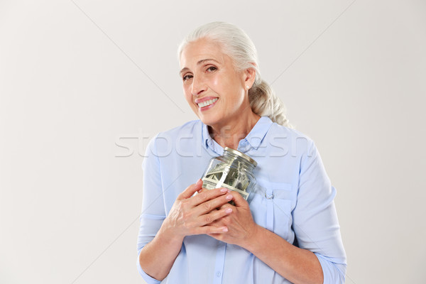 Happy smiling mature woman hugging her glass jar with dollars Stock photo © deandrobot